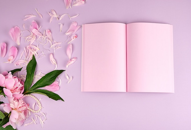 Open blank notebook with pink sheets and blooming peonies
