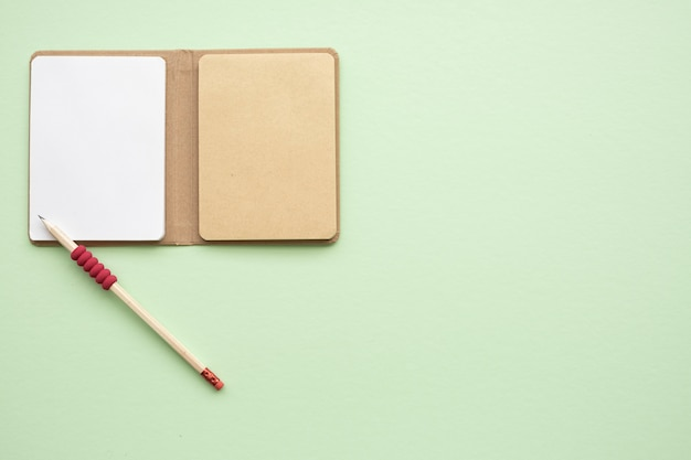 Open blank  notebook with wooden pencil on green background, top view