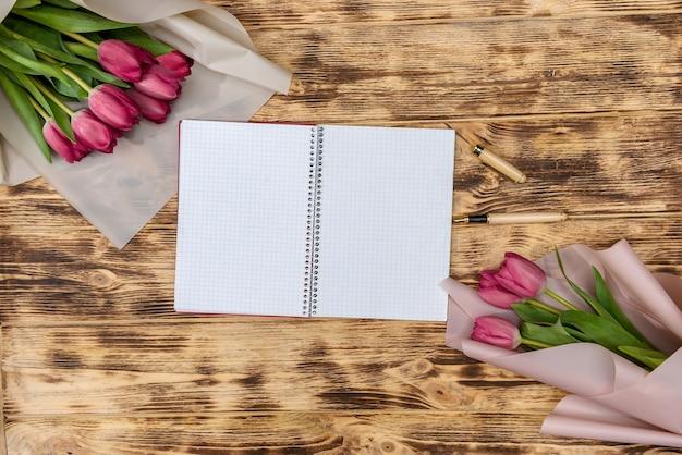 Открытый пустой блокнот и букет цветов розового тюльпана