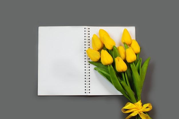 빈 메모장을 열고 노란 튤립 꽃의 꽃다발