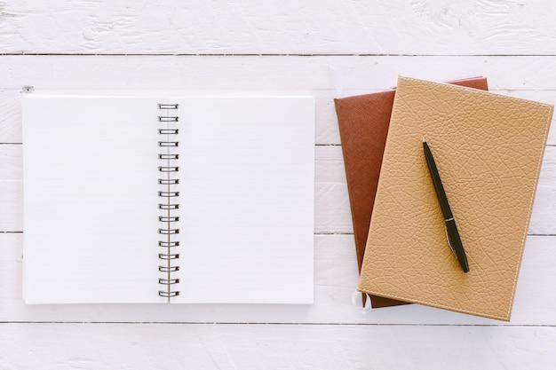 나무 테이블에 빈 흰색 페이지와 빈 메모장을 엽니 다