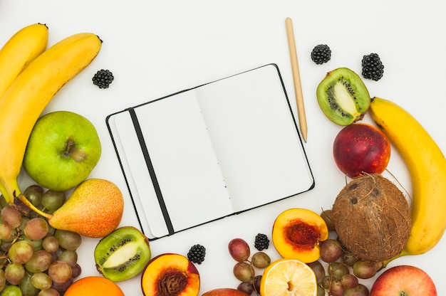 An open blank page notebook; pencil and many fruits on white background
