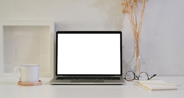 Open blank screen laptop on white wooden table