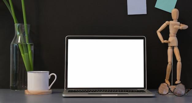 オフィスの装飾が施された空白の画面のラップトップを開く