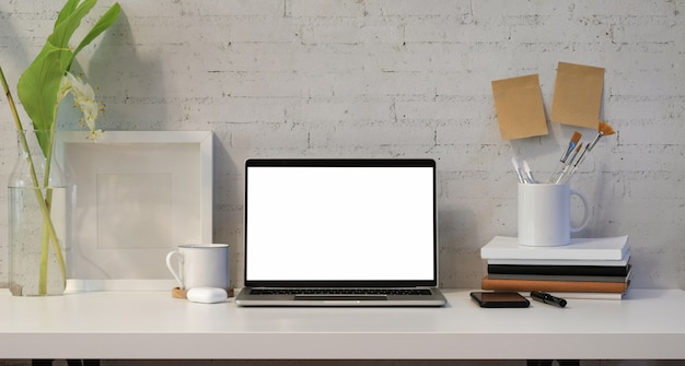 Open blank screen laptop with office supplies