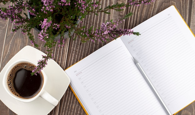 Open a blank white notebook, pen and cup of coffee on the wooden background