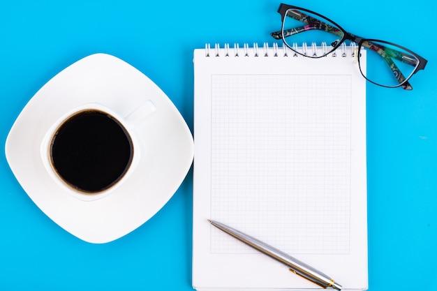 青いテーブルの上にペン、グラス、コーヒーを入れて、空白の白いノートを開きます