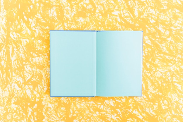 An open blue pages notebook on yellow textured backdrop