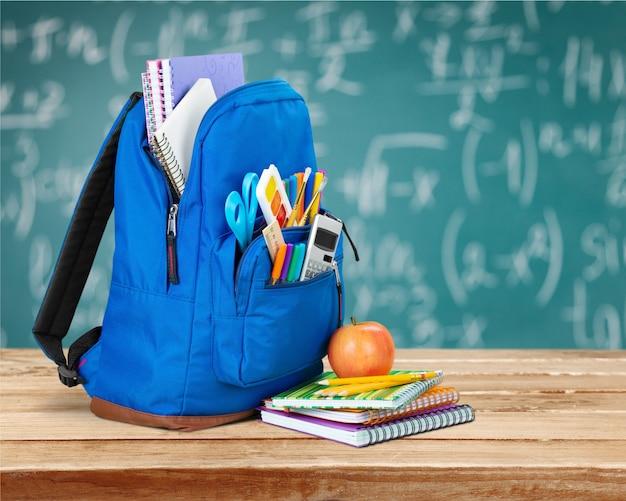 Открытый синий школьный рюкзак и тетрадь с яблоком