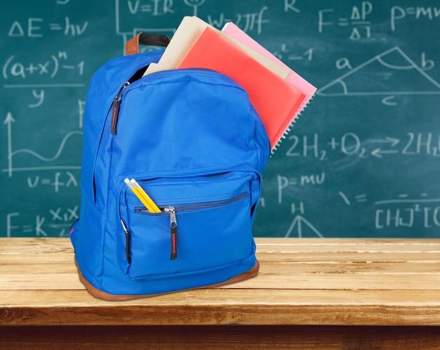 Открытый синий школьный рюкзак и школьная парта с текстом и формулами