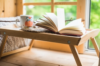 Open book and coffee cup on table near window