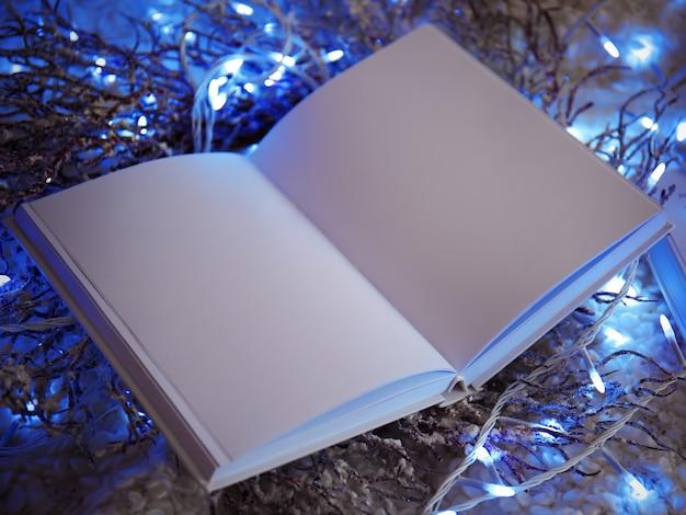 白い格子縞の開いた本と装飾的な花輪