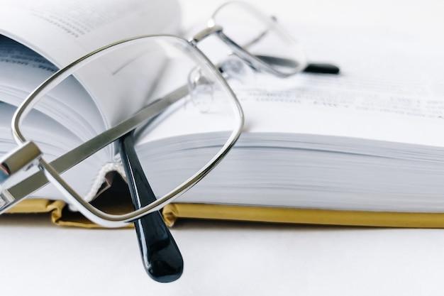 Открытая книга и очки, крупный план.