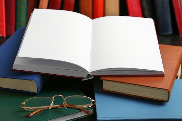 テーブルの上で本とメガネを開く