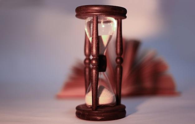 복사 공간이 있는 노란색 background.photo에 책과 hourglass.isolated를 엽니다.