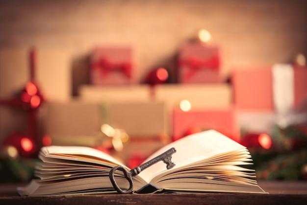 Открытая книга и ключ с рождественскими подарками на фоне