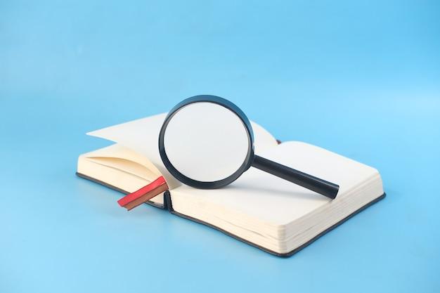 Открытая книга и увеличительное стекло на синем фоне