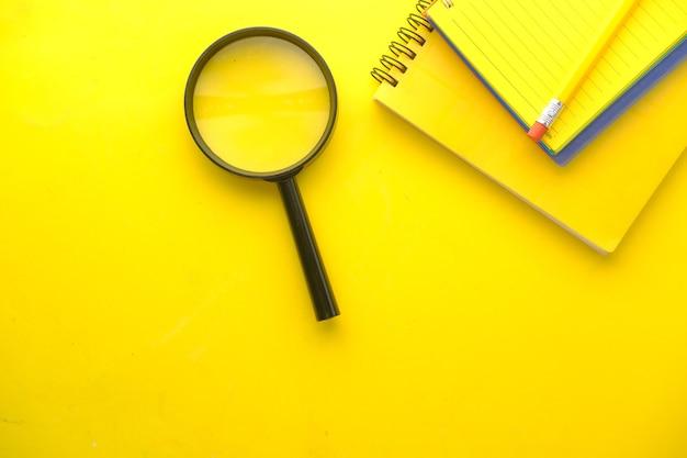 Открытая книга и увеличительное стекло на желтой поверхности