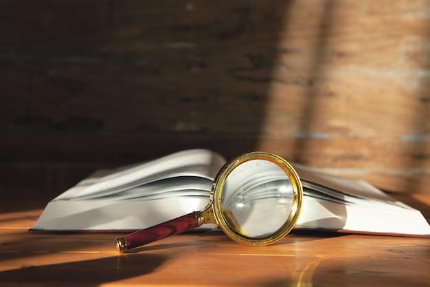 Открытая книга и увеличительное стекло. поиск книг. изучение материала
