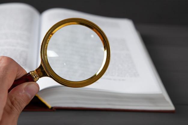 Открытая книга и увеличительное стекло