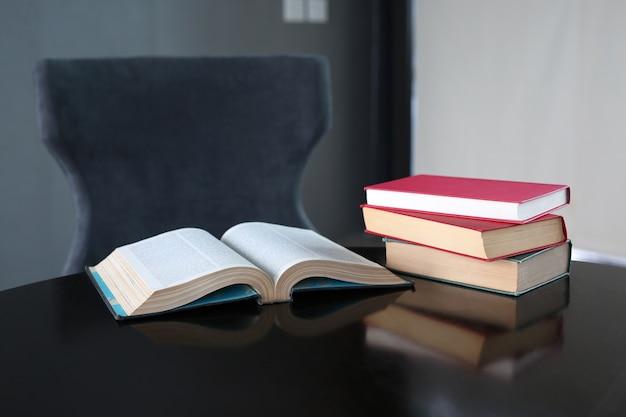 木製のテーブルの本とハードカバーの本の積み重なった本。