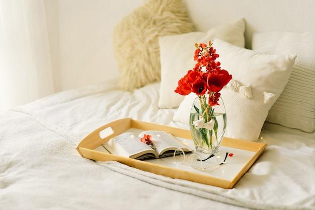 ベッドのトレイに本と花瓶の赤いチューリップを開きます