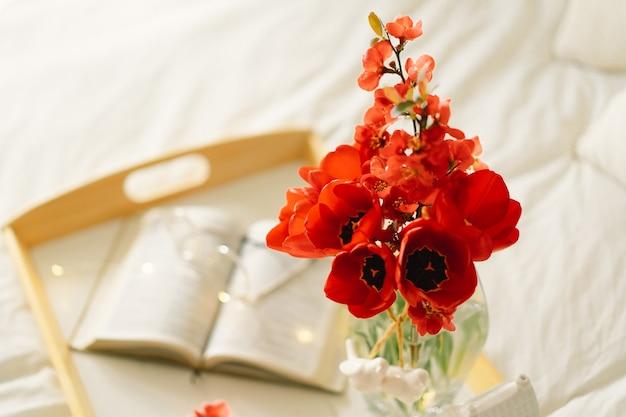 ベッドの上で本と花瓶の赤いチューリップを開く