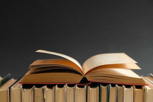 Open book on black background, hardback books on wooden table. education and learning.