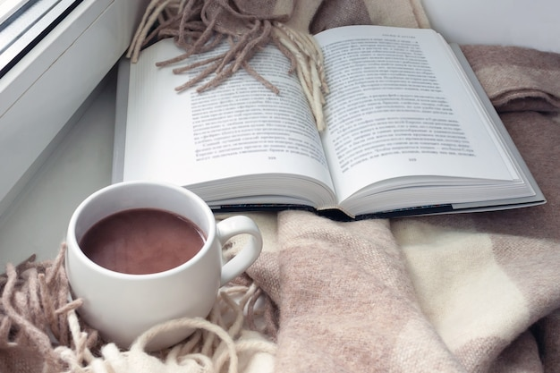 Open book, blanket, a cup of cocoa on the windowsill