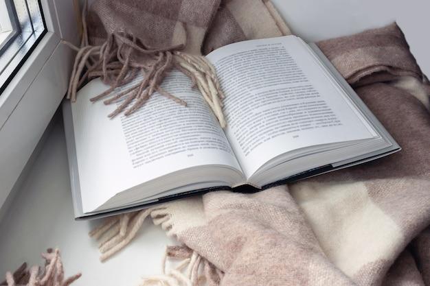 An open book, a blanket on the windowsill