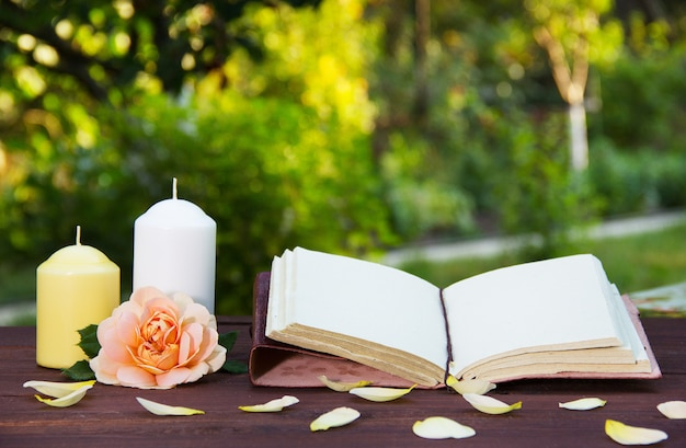 Открытая книга, свеча и ароматная роза. романтическая концепция.