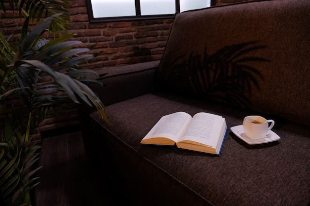 Open book and cbright studio lighting in the interior of the room. film light.ap of coffee on sofa. dark interior.