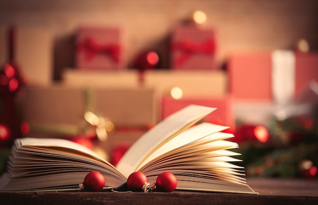 Open book and christmas gifts on background
