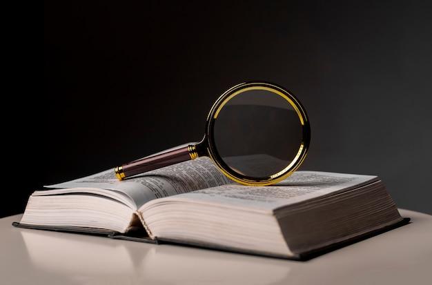 Крупный план открытой книги с переворачиванием страниц и увеличительной лупой. учебник в твердом переплете на столе. концепция обучения и исследования.