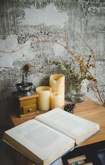 Open book, coffee grinder on wooden table, focus on candles