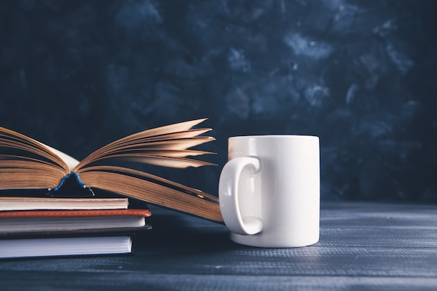An open book and a cup on the table