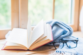 Open book, eyeglasses and blue blanket near the window