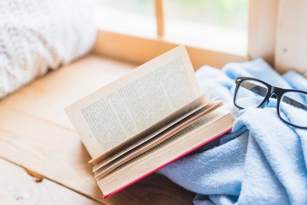 Apra il libro e gli occhiali sulla coperta blu sopra la tabella