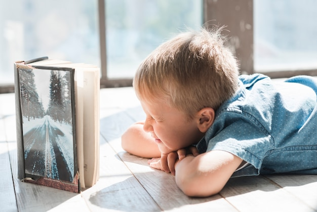 An open book in front of boy closing his eyes