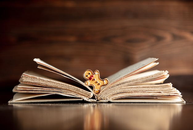Open book and gingerbread man on wooden table