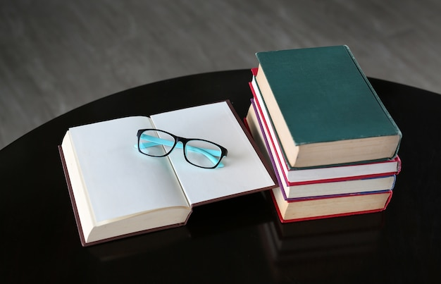 Open book, hardcover books and glasses on wooden table