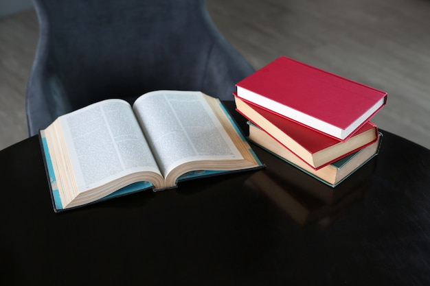Open book and hardcover books on wooden table in library