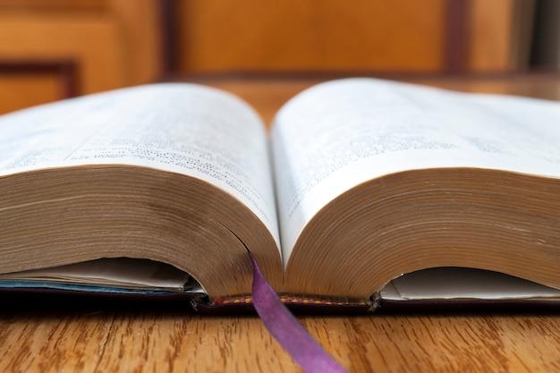 黄色の木製の背景に開いた本聖書 Premium写真
