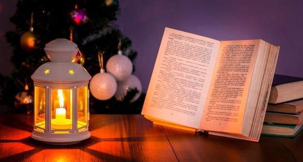 クリスマスツリーの下にあるランタンに照らされた開いた本_