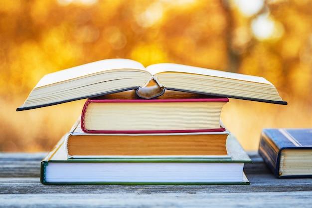 Открытая книга в стопке книг на столе в осеннем парке.