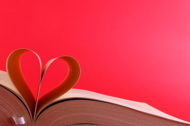 An open book and its pages form a heart isolated on a red background