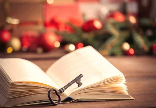 Open book and key with christmas gifts on background