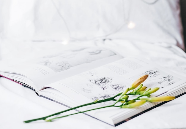 An open book lies on the bed with a flower-lily