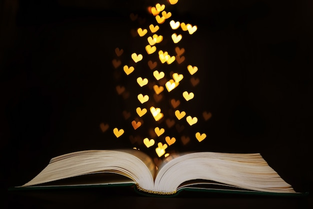 An open book lies on a dark , above the book are the lights of a garland in the shape of hearts.
