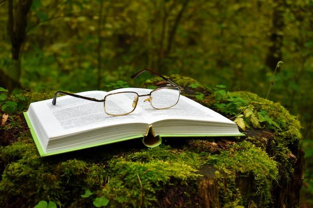 Открытая книга лежит на пне в лесу. очки и книга в парке